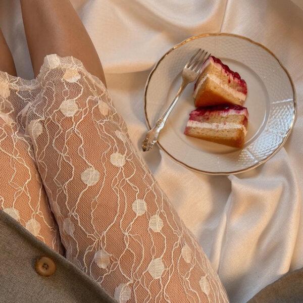 Neben einer sitzenden Frau liegt ein Stück Kuchen auf einem Teller