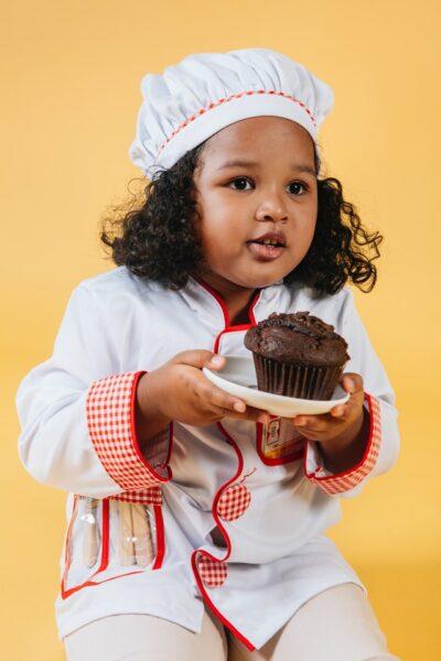 Ein Mädchen in Kochoutfit hält einen Schokoladenmuffin
