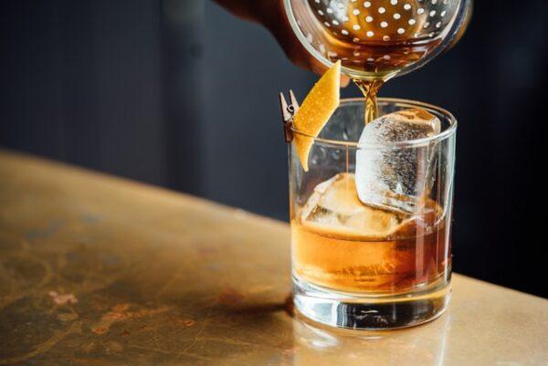 Jemand gießt Rum in ein Glas mit einem Eiswürfel darin