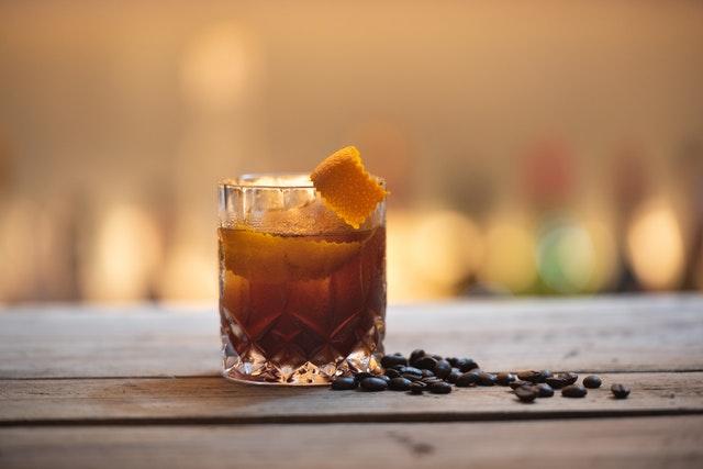 Neben einem Glas Rum liegen einige Kaffeebohnen