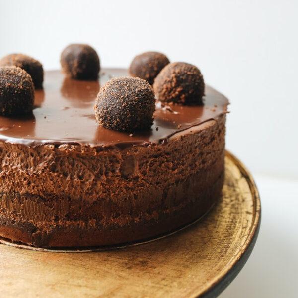 Eine Schokoladentorte mit kleinen Rumkugeln darauf