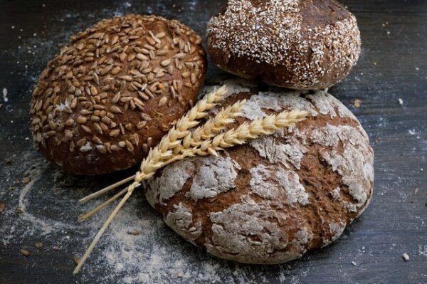 Drei Brote auf denen Getreide liegt und Mehl darum