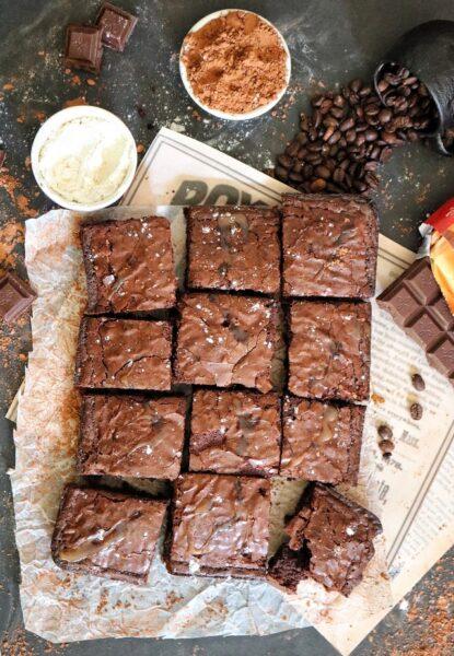 Einige Brownies liegen auf Backpapier. Drumherum Schokolade, Schüsseln mit Zutaten und Kaffeebohnen.