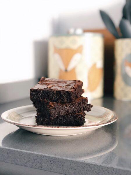 Saftige Brownies gestapelt auf einem Teller. Im Hintergrund sieht man eine Keksdose.
