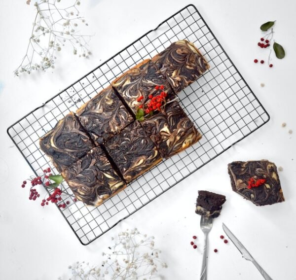 Brownies mit einem marmorierten Topping auf einem Metallgitter. Daneben wurde bereits mit Messer und Gabel ein Stück angeschnitten. Alles ist mit weißen und roten Blumen geschmückt