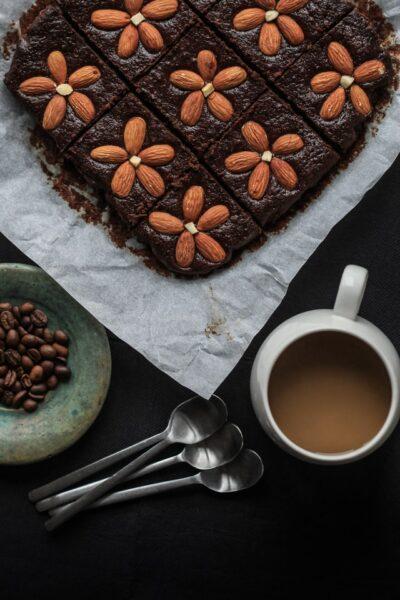 Auf einem Blech: Brownies mit Mandeln, die wie Blumen gelegt sind. Daneben eine Tasse Kaffee und mehrere Löffel sowie eine Schüssel Kaffeebohnen.