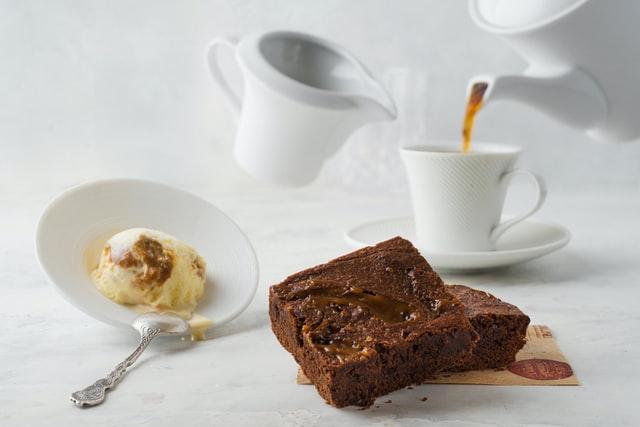 Brownies auf einem weißen Tisch. Dazu eine Kugel Eis und eine Tasse, in die Kaffee und Milch gegossen wird.